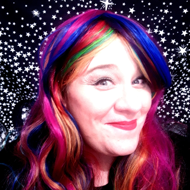A woman with long rainbow hued hair smiles at the camera. She sits in front of a black background filled with white stars.