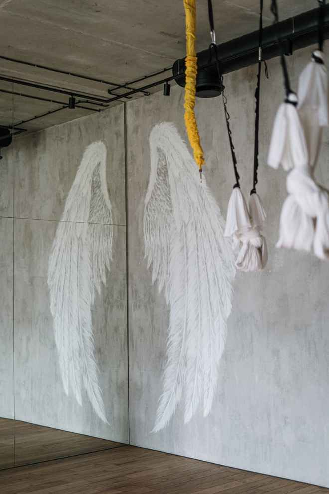 on a concrete wall a wing is painted and is reflected in a joining mirrored wall creating a pair of wings